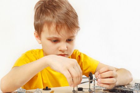 Little serious engineer plays with mechanical constructor at table